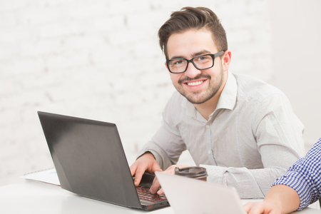 businessman working at his computer: Image of businessman working in office in front of his laptop computer. Happy man in glasses toothy smiling. Stock Photo