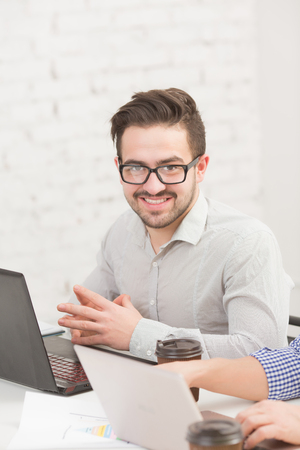 businessman working at his computer: Confident businessman working in front of his laptop computer in office. Happy man in glasses sitting at table and smiling.