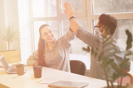 personas comunicandose: el hombre y la mujer independiente feliz que trabaja en oficina en los ordenadores portátiles. Las personas se comunican y hacen chocar los cinco.