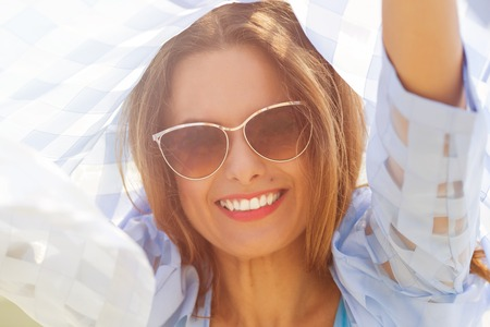 middleaged: Portrait of happy middle-aged woman in the city. Lady in sunglasses holding blue coat over her head outdoors. Toned image.
