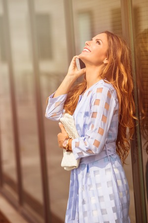 thirties: Beautiful brown-haired woman or businesswoman in her thirties talking on cell phone. Lady looking at the sky and laughing by office building. Toned image. Stock Photo