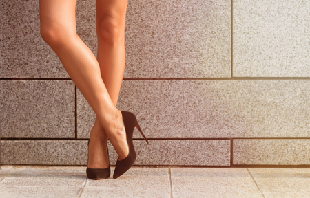 low section view: Beautiful slim and slender womans legs isolated on black high heels. Crossed womans legs isolated on brick wall background. Toned image. Stock Photo