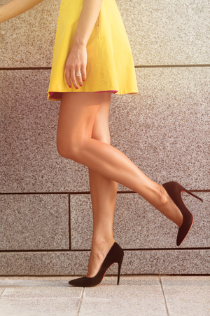 Close-up image of womans legs in profile. Slim and slender legs on black high heels isolated on brick wall background. Toned image.