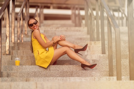 hard day at the office: Fashion girl sitting on stair of office building with orange cocktail. Smiling lady in sunglasses enjoying her time after hard day. Toned image.