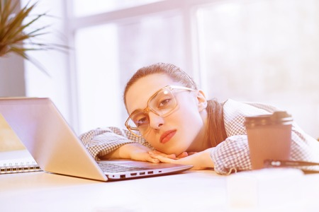 hard day at the office: Toned picture of tired freelance woman lying on laptop computer with opened eyes. Beautiful lady resting after hard working day in office.
