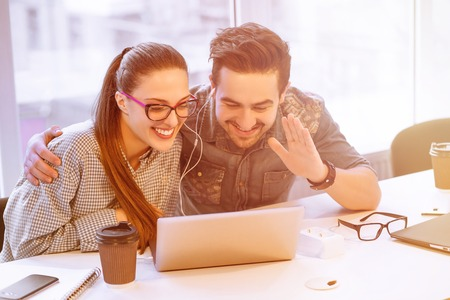 freelancers: Toned picture of happy man and woman freelancers speaking over laptop with their foreign friends, colleagues or partners in office.