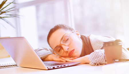hard day at the office: Toned picture of tired and exhausted freelance woman sleeping on laptop computer in office. Beautiful lady resting after hard working day. Stock Photo