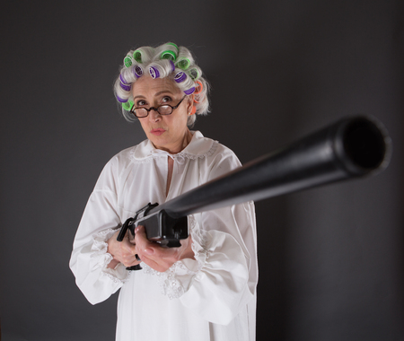 Beautiful grandmother posing with weapon in studio. Serious lady with rollers on looking at camera and holding rifle.