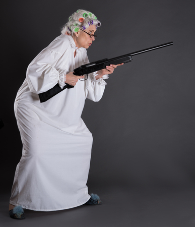 robberies: Serious grandmother posing with rifle in studio imagining that she is protecting her house from robberies. Elderly in defence.
