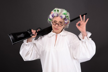 the elderly residence: Grandmother holding rifle and showing okay sign in studio over grey background. Happy elderly in glasses defending her residence. Stock Photo