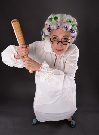 psychotic: Top view of crazy furious grandmother holding criket bat and looking at camera. Beautiful lady with rollers on in studio. Stock Photo