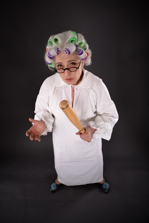 bad temper: Top view of crazy furious grandmother looking at camera while holding criket bat in studio. Studio shot of excited and astonished senior lady.