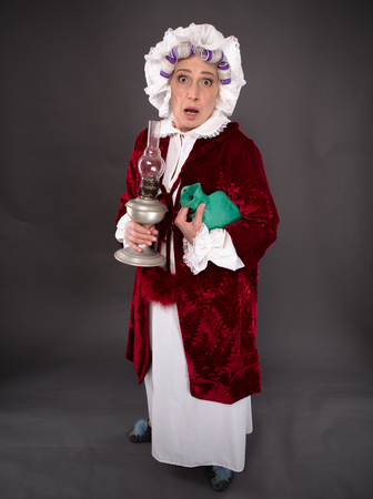 the elderly residence: Top view of grandmother posing with petroleum-lamp during robbery of residence. Beautiful elderly woman looking at camera. Stock Photo