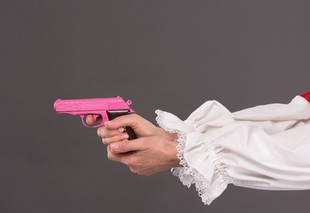 womans clothing: Close-up picture of pink plastic gun represented by woman in white long-sleeved clothing. Childs toy in womans hands. Stock Photo