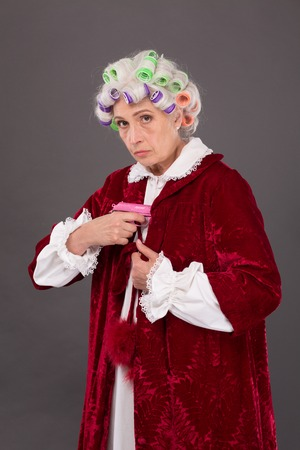 demanding: Strict and demanding elderly lady with rollers on hiding pink plastic gun under blouse in studio. Studio shot. Serious glance. Stock Photo