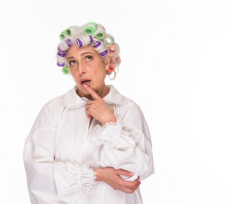 Thoughtful senior lady posing over white background and looking upwards in studio. Modern grandmother with rollers on posing for photographer for fashion magazine. Zdjęcie Seryjne