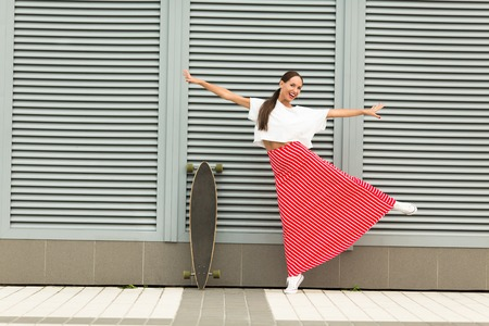 sidewards: Photo of hipster lady in full length having fun, the longboard near by her. Cheerful lady in white T-shirt and long stripped red skirt posing with arms extended sidewards.