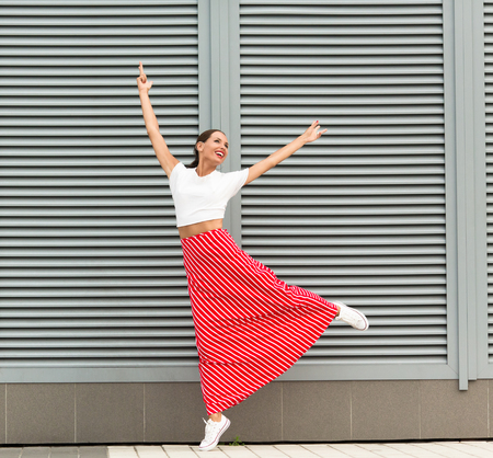 Beautiful lady with red lips happy dancing on the street. Woman in white T-shirt, long stripped red skirt and white gumshoes smiling with her arms raised.