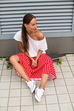 after hours: Hipster lady sitting on longboard after hours riding. Happy long-haired girl in white T-shirt, red stripped skirt and white gumshoes resting.
