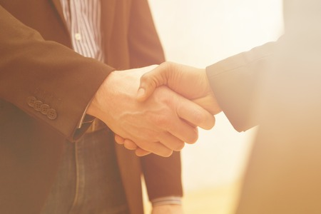 firms: Business handshake of two men demonstrating their agreement to sign agreement or contract between their firms  companies  enterprises.