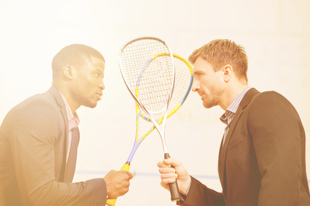business game: Two businessmen in business suits holding rackets and standing face to face before battle - match in squash on court.