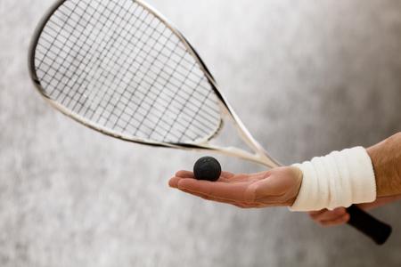스쿼시 라켓 및 남자의 손에 한 공 확대 사진. 법정에있는 사람의 손에 표현 된 검은 색 공. 스톡 콘텐츠