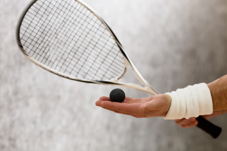 Closeup of squash racket and one ball in man's hand. Black-coloured ball represented on man's hand who is on court.