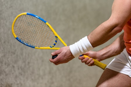 racquetball: Half closeup picture of squash racket in mans hands. Muscular man playing squash on court indoors.