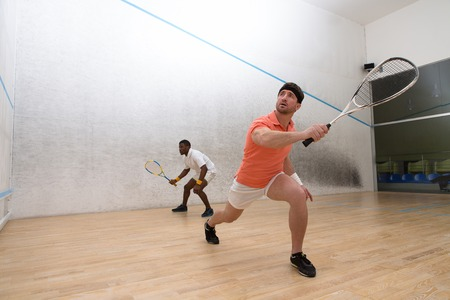 Squash players in action on squash court. Muscular men using rackets for hitting ball. Handsome men doing sports.