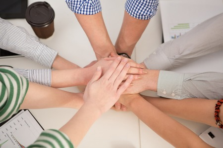 joining hands: Team work concept. Business people joining hands in office. Office workers showing unity and power of their company. Stock Photo