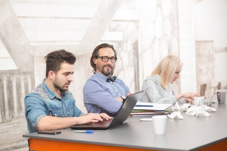 freelancers: Business people working upon business projects in office. Freelancers using laptop computers and sitting at table. Stock Photo