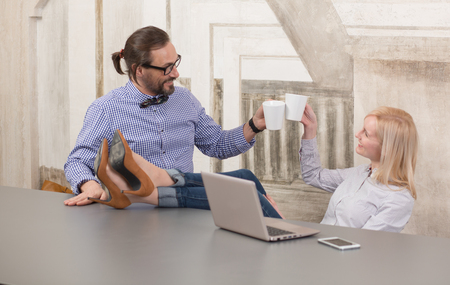 people communicating: New corporate partners toasting coffee at office after finalizing business deal. Happy people communicating and looking face to face. Stock Photo