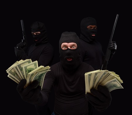 gangster background: Portrait of gangster showing money stolen from house, apartment, flat, etc. Thieves in masks over black background. Isolated on black.