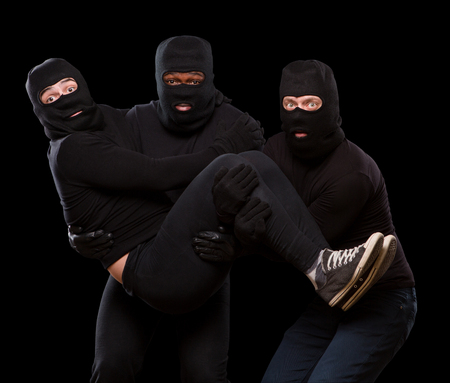 robberies: Picture of three handsome thieves or robberies in balaclavas over dark grey background. Dangerous man holding another man in arms. Isolated on black.