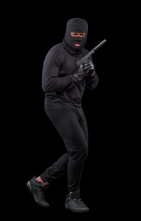 housebreaking: Male thief in mask posing in full length while holding gun pointing up isolated over grey background in studio. Isolated on black.