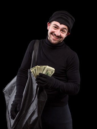 burglary: Burglar is carying full bag of money and smiling for camera over dark grey background. Handsome gangster after burglary of house, apartment or flat. Isolated on black. Stock Photo