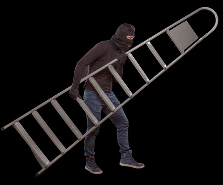 burglary: Masked thief slealing ladder from house. Swindler using ladder for burglary or robbery. Mafia concept. Isolated on black. Stock Photo