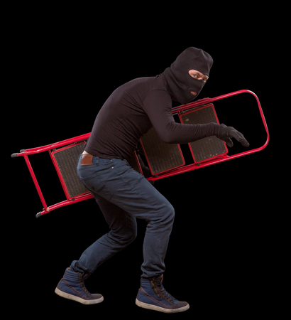 housebreaking: Masked thief using little ladder for his actionsconnected with robbery or burglary of house, apartment or flat. Studio shot. Mafia concept. Isolated on black.