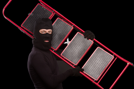 housebreaking: Portrait of masked thief posing with ladder over black background. Young man in balaclava going to rob house, apartment or flat. Isolated on black.