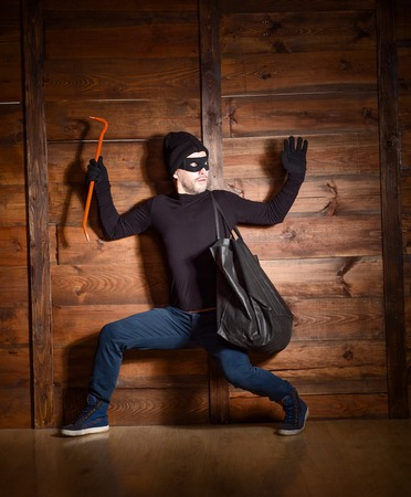 felony: Masked burglar wearing black clothes was caught by police near house in which he wanted to break in. Stock Photo