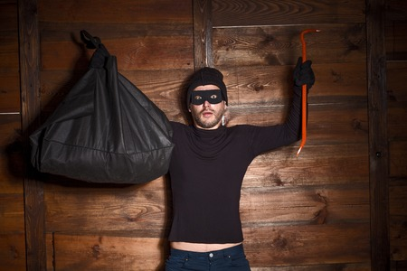 felonious: Catch burglar concept, thief with balaclava caught in front of wooden wall of someones house. Man standing with his hands up.