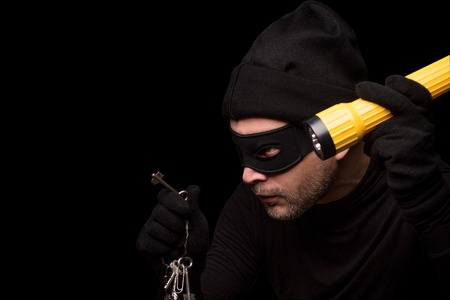 scammer: Thief with robbery mask holding flashlight behind over black background. Man in black clothes holding keys from expensive house. Isolated on black. Stock Photo