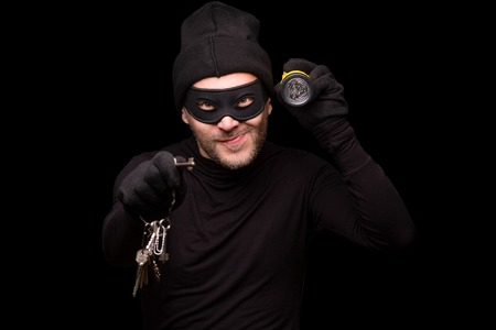 scammer: Portrait of masked thief holding flashlight and keys. Handsome man looking at camera over black background. Isolated on black.