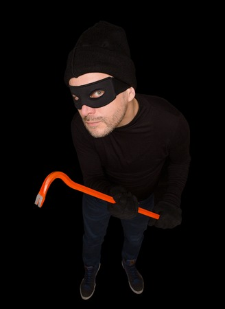 felonious: Funny masked robber or thief. View from top or from hidden camera. Handsome man holding crowbar over black background. Isolated on black.