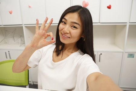 Asian student showing okay sign to camera while making selfies in library. Happy brunette lady posing on selfie in library or office.