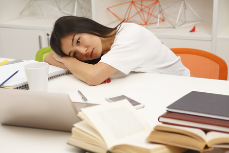 Tired Asian student resting after hard-working day in library. Exhausted woman lying on table with her eyes opened. Stock Photo - 57177983