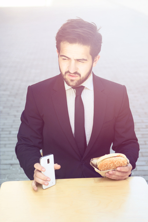 devour: Toned portrait of handsome businessman eating junk food and holding mobile or smart phone while having break in cafe during his work.