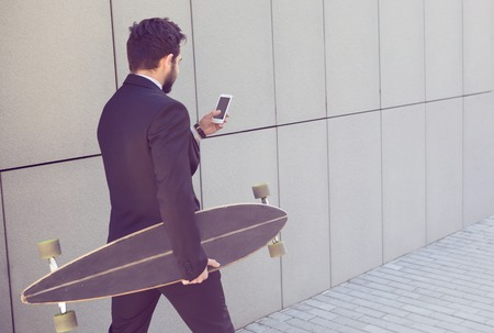 Toned portrait of handsome businessman walking with longboard and mobile phone. Freelance man in black business suit going to work.