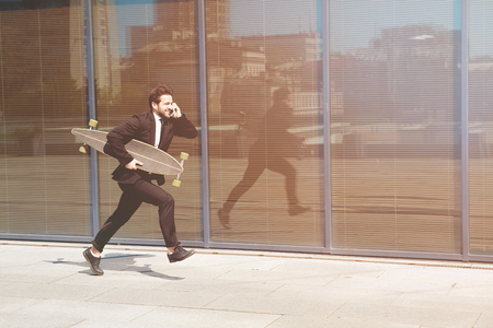 hurrying: Hurrying to work. Toned picture of full length of young businessman looking forward while running along street and speaking over mobile phone.