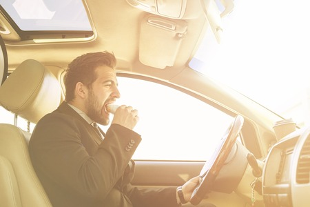 hurrying: Toned picture of handsome businessman eating junk food while driving to work. Freelance man hurrying in morning to do many things. Stock Photo
